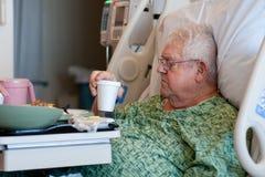 De bejaarde mannelijke het ziekenhuispatiënt drinkt water Royalty-vrije Stock Foto