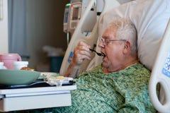 De bejaarde mannelijke het ziekenhuispatiënt eet lunch Stock Afbeeldingen