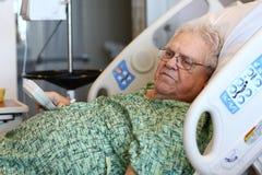 De bejaarde mannelijke het ziekenhuispatiënt houdt TV ver Royalty-vrije Stock Afbeeldingen
