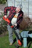 De bejaarde mannelijke randen van het tuinman in orde makende gras. Stock Fotografie