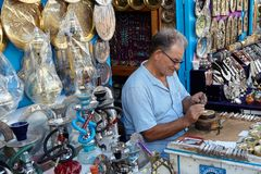 De bejaarde meester maakt een mooi stuk van koper met chasin Stock Foto's
