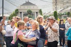 De bejaarde mensen dansen op de straat Stock Foto