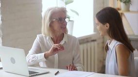 De bejaarde mentor en de onervaren advocaat die vormen contractdetails samenwerken stock footage