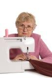 De bejaarde naait op de naaimachine Royalty-vrije Stock Afbeeldingen