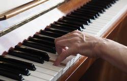De bejaarde persoonshand die de piano spelen, sluit omhoog royalty-vrije stock afbeelding