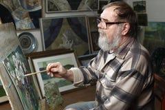 De bejaarde schilder met baard en glazen trekt een bloemenbeeld door olieverf in kunstworkshop Royalty-vrije Stock Afbeeldingen