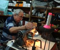 De bejaarde schoenmakerswerken in zijn workshop stock afbeelding