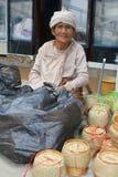 De bejaarde verkoopster verkoopt rieten manden voor rijst in Vientiane Laos Royalty-vrije Stock Afbeeldingen