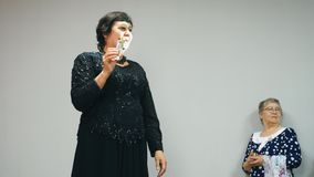 De bejaarde vette vrouw in zwarte kleding houdt een parfumpresentatie van nieuw parfum stock videobeelden
