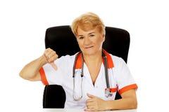 De bejaarde vrouwelijke arts of verpleegster zitting achter het bureau en toont neer duim Stock Foto