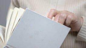 De bejaarde vrouwelijke gepensioneerde die in glazen boek lezen in vrije tijd, hobby en ontspant stock footage