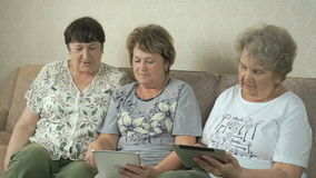 De bejaarden bekijken foto's gebruikend digitale tabletten stock video