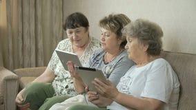De bejaarden bekijken foto's op het scherm van tabletten stock footage