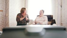 De bejaarden gingen zitten om op TV te ontspannen en te letten stock footage