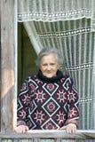 De bejaarden glimlachen vrouw kijken uit open venster van Stock Foto's