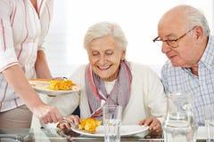 De bejaarden koppelen het eten van lunch Stock Foto's