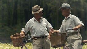 De bejaarden met de fietsen hebben een gesprek stock videobeelden
