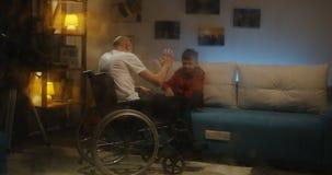 De bejaarden wheelchaired de mens die aan zijn kleinzoon spreken stock video