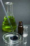 De beker van het laboratorium die met groene kleuren vloeibare substanties wordt gevuld Stock Afbeelding