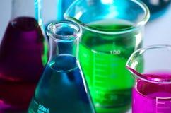 De bekers van het chemielaboratorium bevattende roze, blauwe en groene oplossingen op een nadenkende oppervlakte stock foto's