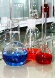 De bekers van het laboratorium met de gekleurde vloeistof Stock Foto