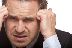De beklemtoonde bedrijfsmens heeft slechte hoofdpijn in bureau Royalty-vrije Stock Foto's
