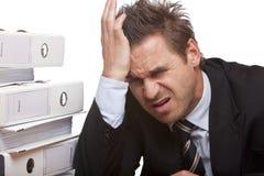 De beklemtoonde bedrijfsmens heeft slechte hoofdpijn in bureau Stock Fotografie