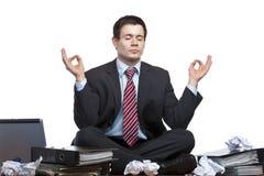 De beklemtoonde bedrijfsmens mediteert bij bureau in bureau Royalty-vrije Stock Afbeeldingen