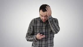 De beklemtoonde jonge mens schokte verrast die, en, vervult gestoord door wat hij op zijn celtelefoon op gradiëntachtergrond ziet stock videobeelden