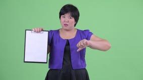 De beklemtoonde jonge te zware Aziatische klembord tonen en vrouw die beduimelt neer geven stock video