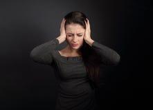 De beklemtoonde ongelukkige bedrijfsvrouw sloot oren de handen omdat nr stock fotografie