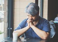 De beklemtoonde vermoeide jonge Aziatische mens op middelbare leeftijd, bejaarde neemt hand op hoofd voelend depressie en uitgepu stock foto's