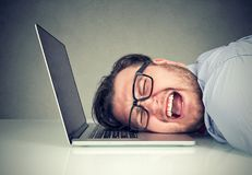 De beklemtoonde zitting van de werknemersmens bij bureau met hoofd bij laptop overgewerkt en wanhopig voelen stock foto's