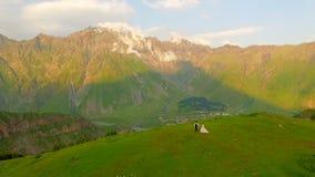 De bekoorde jonggehuwden lopen in de avond in de weide tegen de achtergrond van mooie bergen stock videobeelden