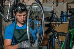 De bekwame fietswerktuigkundige in een workshop herstelt een fiets royalty-vrije stock afbeeldingen