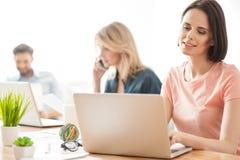 De bekwame jonge medewerkers gebruiken hun computers royalty-vrije stock foto