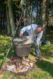 De bekwame kok bereidt soep over de brand voor Stock Foto's