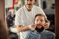De bekwame mannelijke kapper dient zijn cliënt Royalty-vrije Stock Afbeeldingen