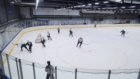 De bekwame strijd van hockeyspelers voor puck met stokken bij spel stock footage