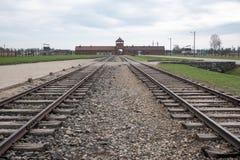 De belangrijkste ingang die aan die Auschwitz Birkenau Nazi Concentration Camp de treinsporen tonen worden gebruikt om Joden aan  royalty-vrije stock foto