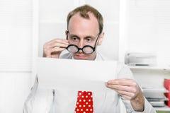 De belastingsadviseur controleert bedrijfsaantallen met grote glazen Stock Afbeeldingen