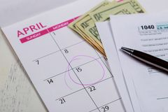 De belastingsdag, dollars en vormt 1040 inkomstenbelastingsvorm die belastingsdag voor April Calendar met woorden tonen royalty-vrije stock foto