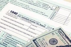 De Belastingsvorm en dollars van de V.S. 1040 - studioschot Gefiltreerd beeld: kruis verwerkt uitstekend effect Stock Foto's