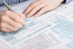 De Belastingsvorm van de V.S. 1040 - mannetje die belastingsvorm invullen - studioschot Stock Foto