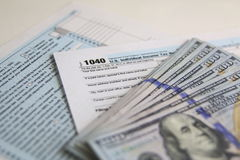 De Belastingsvorm 1040 van de V.S. met nieuwe 100 Amerikaanse dollarsrekeningen Stock Fotografie