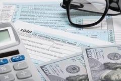 De Belastingsvorm 1040 van de Verenigde Staten van Amerika met calculator, dollars en glazen Royalty-vrije Stock Afbeeldingen