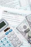 De Belastingsvorm 1040 van de Verenigde Staten van Amerika met calculator en Amerikaanse dollars - sluit omhoog studioschot Royalty-vrije Stock Afbeeldingen