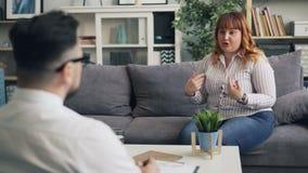 De beledigde vrouw met zwaarlijvigheidsprobleem spreekt aan therapeut die woede uitdrukken stock video