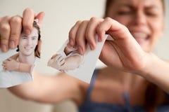 De beledigde vrouw scheurt foto met haar vriend royalty-vrije stock afbeelding