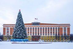 De beleidsbouw en de Nieuwjaarboom in de winterscène stock foto's